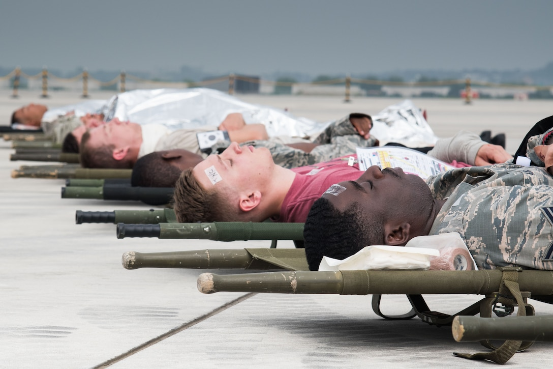 Simulated injured personnel rest on the flightline during an emergency management exercise at Osan Air Base, Republic of Korea, Sept. 8, 2016. The victims suffered from injuries ranging from bruises to broken ligaments, which 51st Medical Group personnel were charged to respond to and treat. (U.S. Air Force photo by Senior Airman Dillian Bamman)
