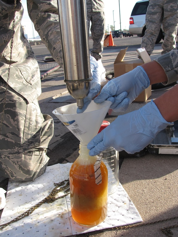 The AFRL Biological Materials and Processing Research Team collects fuel samples from a storage tank to analyze for potential biocontamination.  (U.S. Air Force photo)