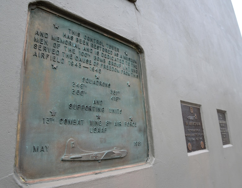"""Three plaques, located near the entrance of the air traffic control tower at the 100th Bomb Group Memorial in Thorpe Abbotts, England, honor the squadrons and units which served from that airfield between 1943 to 1945. During World War II, the 100th BG suffered a tremendous loss during the initial bombing missions, which earned them the nickname, the """"Bloody Hundredth."""" The tower has been reconstructed from the original structure and houses donated artifacts pertaining to the memorial. (U.S. Air Force photo by Senior Airman Justine Rho)"""