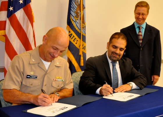 "DAHLGREN, Va. (Sept. 7, 2016) - Capt. Brian Durant and Amit Kapoor sign an exclusive license agreement authorizing First Line Technology LLC to manufacture Navy patented lifesaving decontamination technology for warfighters and first responders. The 'Dahlgren Decon' decontamination solution - developed to defend U.S. troops against chemical, biological, and radiological agents - is protected under several patents by Naval Surface Warfare Center Dahlgren Division (NSWCDD). Durant, NSWCDD commanding officer, and Kapoor, First Line Technology president, emphasized the importance of the technology transfer that will equip first responders across the nation with technology to defend the public from hazardous threats. ""This is the home run of technology transfer and doesn't happen without a lot of contributors,"" said Chris Hodge, NSWCDD scientist and Dahlgren Decon inventor, standing. Hodge and his team worked for more than a decade to develop and test this revolutionary response to chemical and biological warfare agents."