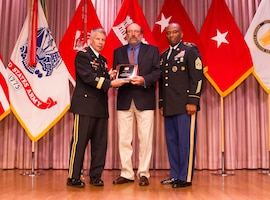 Steve Eggers, center, receives the Don Lawyer Award as the Corps of Engineers regulator of the year recipient from Lt. Gen. Todd T. Semonite, Chief of Engineers and U.S. Army Corps of Engineers commanding general, left, and Command Sgt. Maj. Antonio S. Jones during the 2016 National Awards Ceremony in Washington, D.C., Aug. 4.