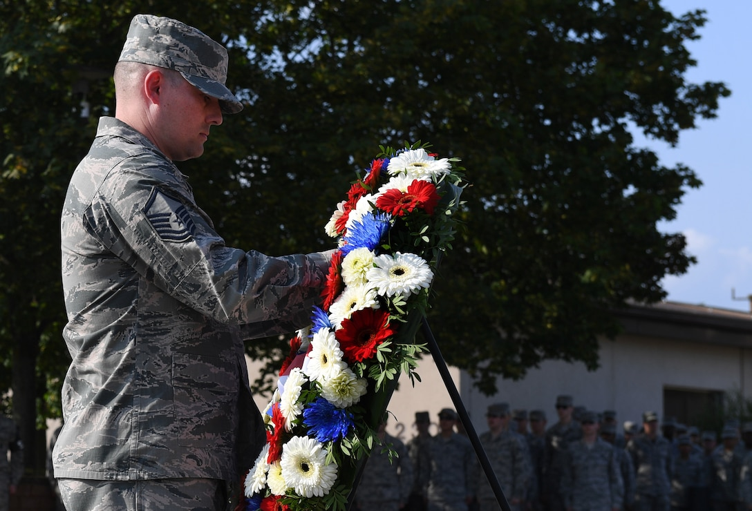 Master Sgt. Jesse Burkard, 86th Civil Engineer Squadron fire protection superintendent, lays a wreath during a 9/11 Memorial Retreat Ceremony Sept. 9, 2016 at Ramstein Air Base, Germany. 2,977 people lost their lives and over 6,000 were injured during the attacks, resulting in one of the largest domestic terrorist attacks in U.S. history. (U.S. Air Force photo/Senior Airman Tryphena Mayhugh)