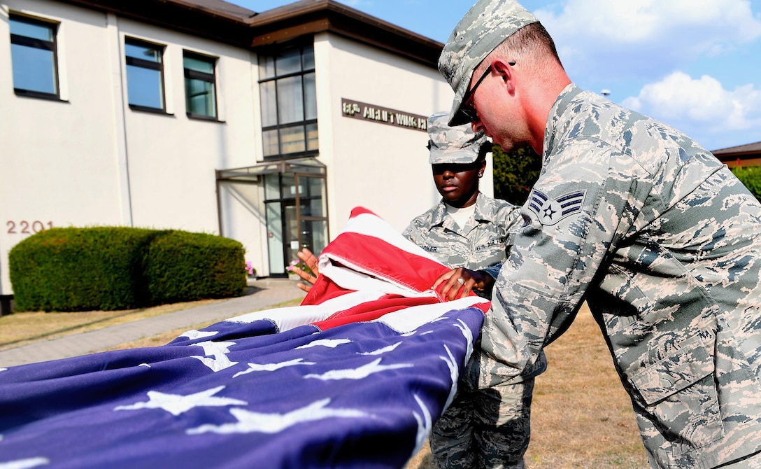 From left, Senior Airman Daneeka Mucker, 86th Logistic Readiness Squadron hazmart pharmacy specialist, and Senior Airman Anthony Tepen, 86th Vehicles Readiness Squadron vehicle maintenance technician, fold the American flag during a 9/11 Memorial Retreat Ceremony Sept. 9, 2016 at Ramstein Air Base, Germany. 2,977 people lost their lives in the attacks, including 343 firefighters, 72 law enforcement officers and 55 military personnel who were first responders at the World Trade Center. (U.S. Air Force photo/Senior Airman Tryphena Mayhugh)