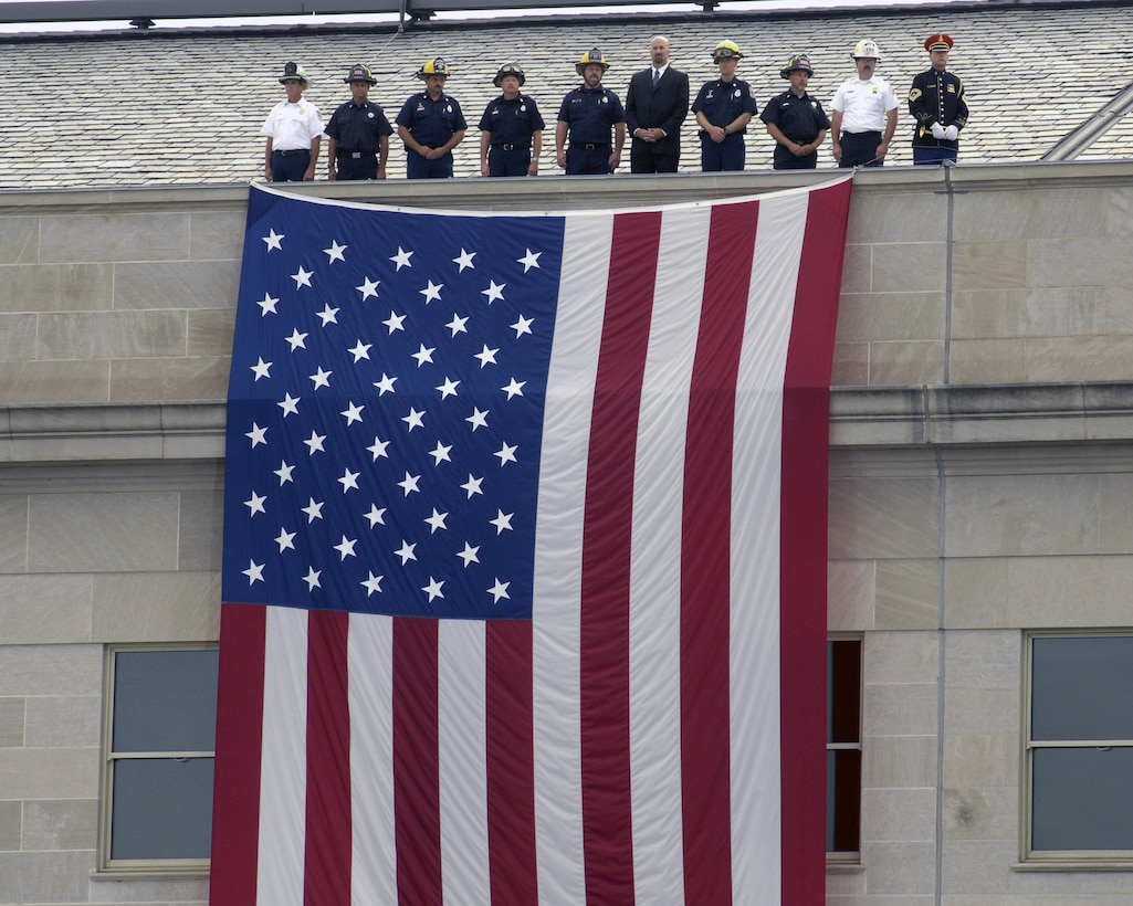 During ceremonies dedicating the Pentagon Memorial, representatives of police and firefighting units who were the first to respond to the 9/11 terrorist attack on the Pentagon, stand at the top of a large American flag suspended from the roof of the Pentagon, Sept. 11, 2008, just as they stood seven years earlier. DoD photo by R. D. Ward