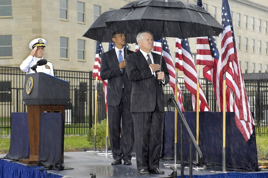 President Barack Obama, center, Defense Secretary Robert M. Gates, right, and Navy Adm. Mike Mullen, chairman of the Joint Chiefs of Staff, salute under rainy skies during a wreath-laying ceremony.