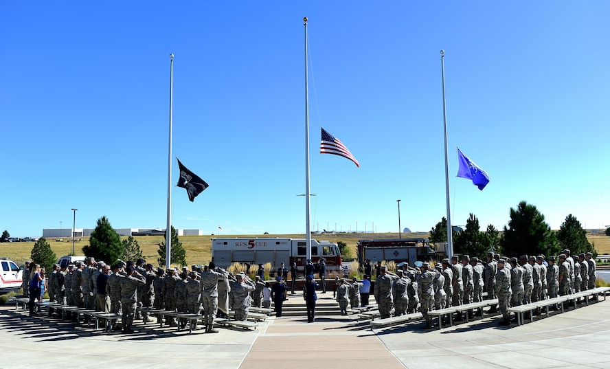 Team Buckley members salute as the national anthem is played during a during a Patriot Day ceremony Sept. 9, 2016, on Buckley Air Force Base, Colo. Patriot Day provides the United States a day of reflecting on the lives lost and paying tribute to the families still recovering from their loss on Sept. 11, 2001. (U.S. Air Force photo by Airman 1st Class Gabrielle Spradling/Released)