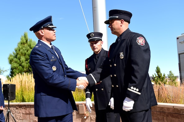 Col. David Miller Jr., 460th Space Wing commander, thanks Buckley Air Force Base firefighters for their service during a Patriot Day ceremony Sept. 9, 2016, on Buckley AFB, Colo. The attacks from Sept. 11, 2001, have greatly impacted the United States' national security, along with national and international politics. (U.S. Air Force photo by Airman 1st Class Gabrielle Spradling/Released)