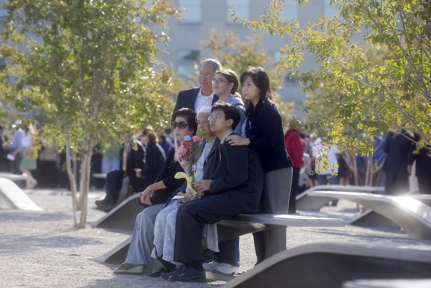 Family members sit on a memorial bench commemorating a loved one who died in the Pentagon during the 9/11 terrorist attack.