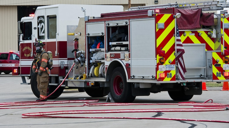 A 5th Civil Engineer Squadron firefighter waits by the fire truck during a fuel spill exercise at Minot Air Force Base, N.D., Sept. 8, 2016. During the annual training, three firefighters posted by the fire truck maintain communication with six firefighters who try to contain the fuel spill. (U.S. Air Force photo/Airman 1st Class Jonathan McElderry)