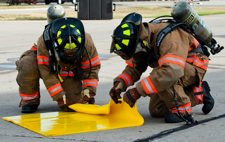 Firefighters with the 5th Civil Engineer Squadron roll up a spill absorbent pad during a fuel spill exercise at Minot Air Force Base, N.D., Sept. 8, 2016. The yellow pads are used to stop the fuel spill immediately while the firefighters use blue pads to absorb the liquid, which was part of the annual training the firefighters received. (U.S. Air Force photo/Airman 1st Class Jonathan McElderry)