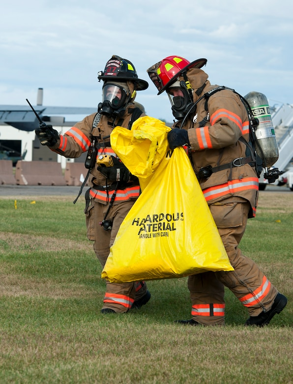 Firefighters with the 5th Civil Engineer Squadron collect simulated contaminated material at Minot Air Force Base, N.D., Sept. 8, 2016. Firefighters were conducting a fuel spill exercise, which is part of a yearly requirement for them. (U.S. Air Force photo/Airman 1st Class Jonathan McElderry)