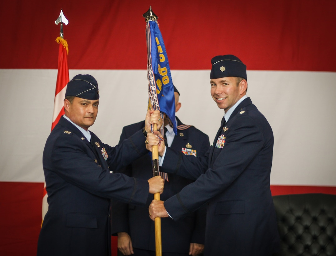 Col. Richard Land, 552nd Operations Group commander, passes the 965th Airborne Air Control Squadron guidon to Lt. Col. Alan Avriett Jr. during change of command ceremonies held Sept. 7 in Hangar 230, Dock 2.  In his previous assignment, Lieutenant Colonel Avriett was the director of operations for the 960th AACS. He is a senior air battle manager with more than 2,200 hours of flying in the E-3B/C/G and the E-8C aircraft, including 1,400 combat hours. (Air Force photo by Senior Airman Christopher J. Abad)