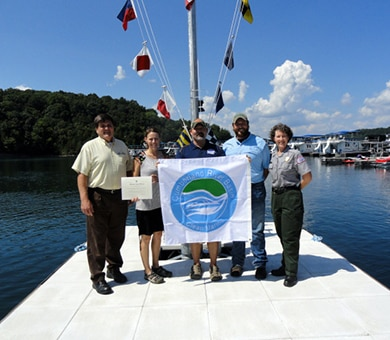 U.S. Army Corps of Engineers Nashville District officials present the Clean Marina flag to April Patterson, owner of Mitchell Creek Marina at the marina on Dale Hollow Lake Aug. 26, 2016.