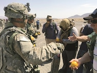 Civil affairs Soldiers attached to the 1st Armored Brigade Combat Team, 1st Infantry Division, pass out oranges to role players during a refugee movement exercise at Fort Irwin's National Training Center Aug. 1. The brigade used the enablers, who were specialists from cyber warfare, civil affairs, electronic warfare and psychological warfare, to conduct a multitude of operations that included defending the brigade's valuable computer network, conducting civilian populous influencing operations and including civilian considerations into battle planning.
