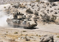 "Soldiers from the 1st Armored Brigade Combat Team, 1st Infantry Division, move their M2 Bradley Infantry Fighting Vehicle along the battlefield during a training mission at Fort Irwin's National Training Center Aug. 8. The ""Devil"" brigade's training at NTC held from the end of July into mid-August focused on a wide range of unified land operations in a new environment away from the comfort of their home station."