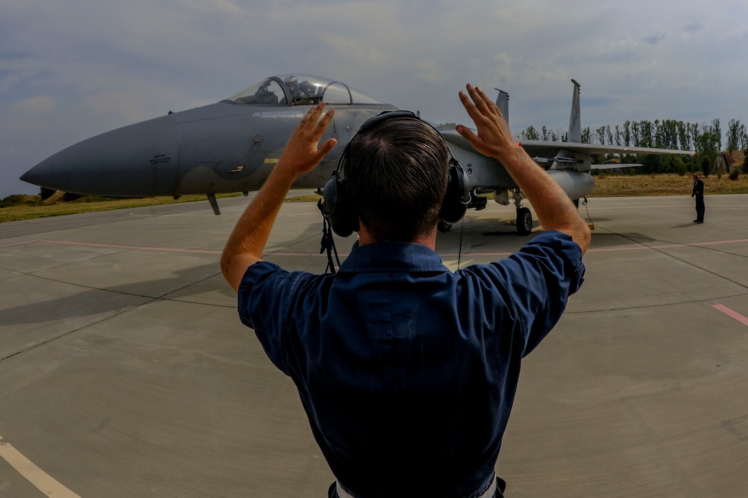 California Air National Guard Staff Sgt. Zechery Blackburn, a 194th Expeditionary Fighter Squadron crew chief, signals to the pilot of an F-15C Eagle fighter aircraft on the flightline at Graf Ignatievo, Bulgaria, Sept. 8, 2016. Four of the squadron's F-15Cs will conduct joint NATO air policing missions with the Bulgarian air force to police the host nation's sovereign airspace Sept. 9-16, 2016. The squadron forward deployed to Graf Ignatievo from Campia Turzii, Romania, where they serve on a theater security package deployment to Europe as a part of Operation Atlantic Resolve. (U.S. Air Force photo by Staff Sgt. Joe W. McFadden)