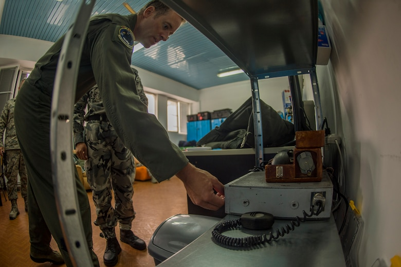 California Air National Guard Lt. Col. Matthew Ohman, a 194th Expeditionary Fighter Squadron F-15C Eagle pilot, tests a radio warning system out of their squadron's flight operations room during joint NATO air policing at Graf Ignatievo, Bulgaria, Sept. 9, 2016. Four California and Massachusetts ANGs' F-15Cs and approximately 75 Airmen from the 194th EFS deployed to Graf Ignatievo, Bulgaria, and will stand ready as interceptors, prepared to quickly react to any violations and infringements for policing of Bulgarian airspace Sept. 9-16, 2016. The squadron forward deployed to Graf Ignatievo from Campia Turzii, Romania, where they serve on a theater security package deployment to Europe as a part of Operation Atlantic Resolve.  (U.S. Air Force photo by Staff Sgt. Joe W. McFadden/Released)