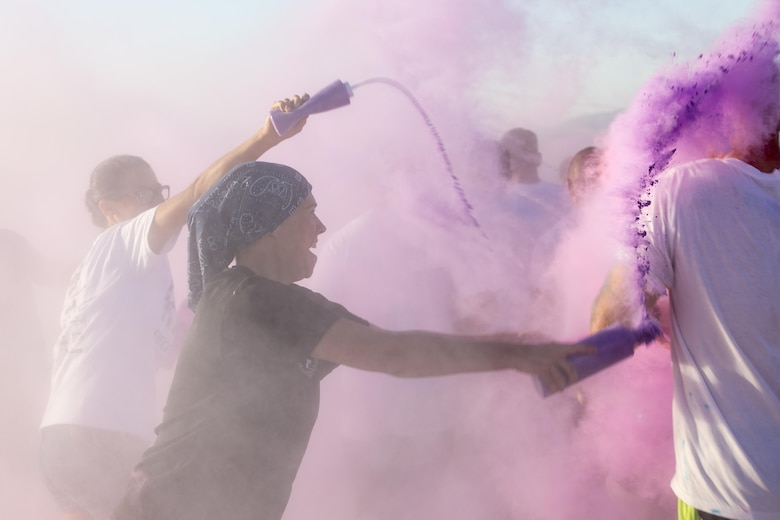 A spouse of a Marine with 1st Battalion, 7th Marine Regiment, throws colored cornstarch on runners during a battalion-wide 5k color run aboard Marine Corps Air Ground Combat Center, Twentynine Palms, Calif., Sept. 2, 2016. (Official Marine Corps photo by Cpl. Levi Schultz/Released)