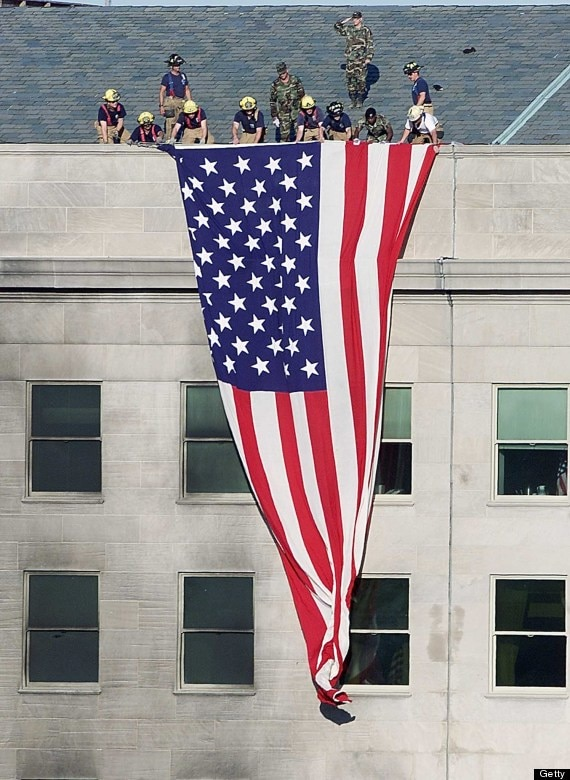 Firefighters and Soldiers unfurl an American flag at the Pentagon Sept. 12, 2001. (Curtsey photo)