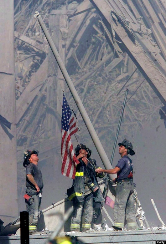 Firefighters raise an American flag at the site of the Twin Towers. (Courtesy photo)
