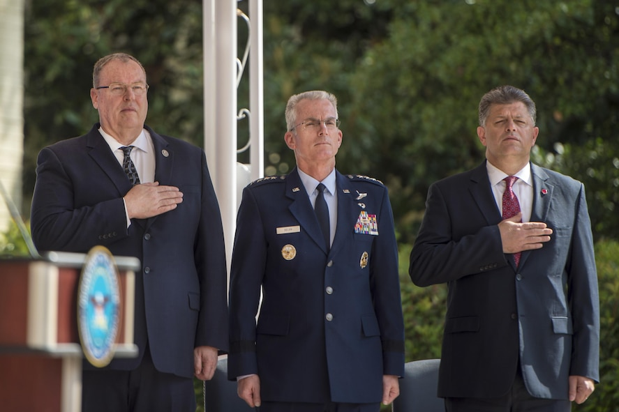 From left, Deputy Defense Secretary Bob Work, Air Force Gen. Paul J. Selva, vice chairman of the Joint Chiefs of Staff; and Michael L. Rhodes, Washington Headquarters Service director of administration and management, honor the flag during a remembrance ceremony.