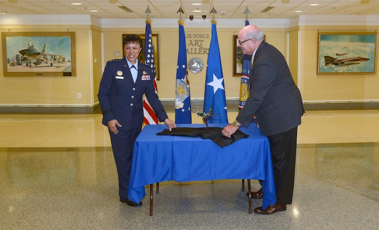 Lt. Gen. Stayce D. Harris, the Air Force assistant vice chief of staff, unveils a model C-7A Caribou with retired Master Sgt. John Schuepbach, a former Caribou administrative specialist, during a ceremony at the Pentagon in Washington, D.C., Sept. 9, 2016. Schuepbach handcrafted and donated this scale model to be placed in the Pentagon's Wings Through Time display. (U.S. Air Force photo/Andy Morataya)