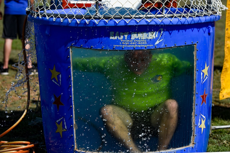 U.S. Air Force Maj. John Travieso, 17th Contracting Squadron commander, drops into a dunk tank during the Combined Federal Campaign kickoff tailgate party at the parade field on Goodfellow Air Force Base, Texas, Sept. 8, 2016. Goodfellow members donated money to take a chance at dunking their commanders to raise money for the CFC. (U.S. Air Force photo by Senior Airman Devin Boyer/Released)