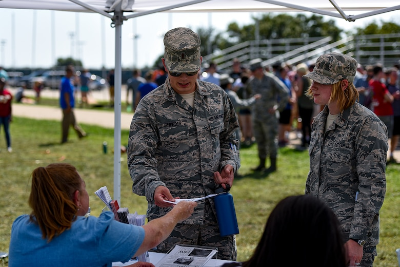 U.S. Air Force officers from the 17th Training Wing visit a non-profit organization's booth during the Combined Federal Campaign kickoff tailgate party at the parade field on Goodfellow Air Force Base, Texas, Sept. 8, 2016. Local non-profit organizations set up booths to give Goodfellow members a chance to donate to their cause as part of the CFC. (U.S. Air Force photo by Senior Airman Devin Boyer/Released)