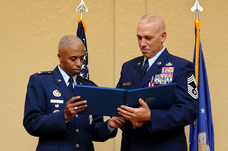 Col. Fred Taylor, Jr., Joint Space Operations Center deputy director and National Reconnaissance Office Liaison, Vandenberg Air Force Base, Calif., presents a certificate of appreciation to Chief Master Sgt. Robert Winters, 81st Training Group superintendent, during his retirement ceremony at the Bay Breeze Event Center Sept. 8, 2016, on Keesler AFB, Miss. Winters retired with more than 29 years of military service and served multiple assignments in California, Louisiana, Georgia, Colorado, Korea and the United Kingdom. He also worked as an electronic warfare officer in support of more than 700 soldiers in multiple locations throughout Iraq. (U.S. Air Force photo by Kemberly Groue/Released)