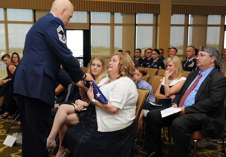 Chief Master Sgt. Robert Winters, 81st Training Group superintendent, presents the U.S. flag to his wife, Terresa, during his retirement ceremony at the Bay Breeze Event Center Sept. 8, 2016, on Keesler Air Force Base, Miss. Winters retired with more than 29 years of military service and served multiple assignments in California, Louisiana, Georgia, Colorado, Korea and the United Kingdom. He also worked as an electronic warfare officer in support of more than 700 soldiers in multiple locations throughout Iraq. (U.S. Air Force photo by Kemberly Groue/Released)