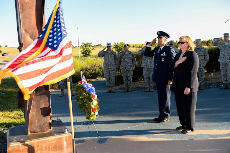 SCHRIEVER AIR FORCE BASE, Colo. -- Col. Anthony Mastalir, 50th Space Wing vice commander, and Geri Satterfield, 50th Space Wing protocol chief, honor the colors during reveille at Schriever Air Force Base, Colorado,  Friday Sept. 09, 2016. Mastalir and Satterfield presented a wreath at the 9-11 artifact display in honor of the 2,996 individuals who died in the attacks.  (U.S. Air Force photo/Christopher DeWitt)