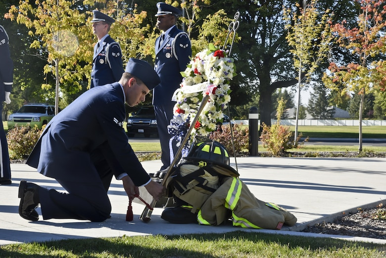 """Airman 1st Class Shawn Mercer, 92nd Civil Engineer Squadron firefighter, places an axe on a display during the Patriot's Day retreat ceremony Sept. 9, 2016, at Fairchild Air Force Base, Wash. Sun. Sept. 11, 2016, marks the 15th anniversary of the deadliest terrorist attack on American soil. The attack was planned and executed by Islamic extremist organization, Al-Qaeda, and ultimately led to the ongoing """"Global War on Terrorism."""" (U.S. Air Force photo/Airman 1st Class Taylor Shelton)"""