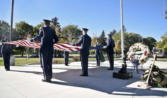 Members from Fairchild Air Force Base honor guard preform a seven man flag fold during the Patriot Day retreat ceremony Sept. 9, 2016, at Fairchild AFB, Wash. For the ceremony, Fairchild members gathered to remember and honor the 2,977 people who lost their lives on Sept. 11, 2001. (U.S. Air Force photo/Airman 1st Class Taylor Shelton)
