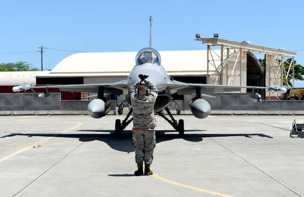 Tech. Sgt. Adam Flood, a crew chief with the 149th Fighter Wing, Texas Air National Guard, headquartered at Joint Base San Antonio-Lackland, Texas, marshals an F-16 Fighting Falcon at Joint Base Pearl Harbor Hickam, Hawaii, Aug. 18, 2016. Flood participated in Sentry Aloha 2016, a large-scale fighter exercise hosted by the Hawaii Air National Guard. (U.S. Air National Guard photo by Tech. Sgt. Rebekkah Jandron)