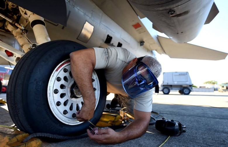 Master Sgt. Dwayne Gore, a crew chief with the 149th Fighter Wing, Texas Air National Guard, headquartered at Joint Base San Antonio-Lackland, Texas, services the tire of an F-16 Fighting Falcon at Joint Base Pearl Harbor Hickam, Hawaii, Aug. 18, 2016. Gore participated in Sentry Aloha 2016, a large-scale fighter exercise hosted by the Hawaii Air National Guard. (U.S. Air National Guard photo by Tech. Sgt. Rebekkah Jandron)