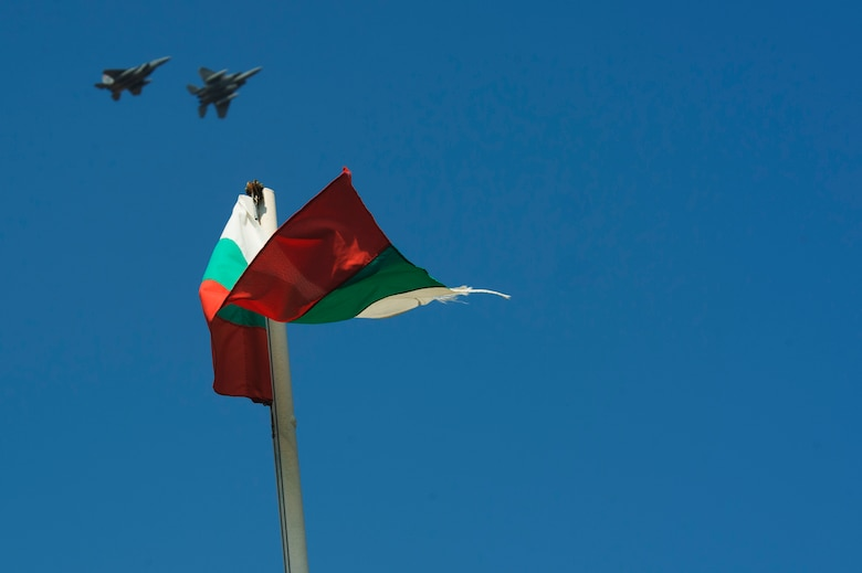 Two California Air National Guard F-15C Eagles fly over a Bulgarian Flag near the flightline at Graf Ignatievo, Bulgaria, Sept. 8, 2016. Four of the 194th Expeditionary Fighter Squadron's F-15C Eagles will conduct joint NATO air policing missions with the Bulgarian air force to police the host nation's sovereign airspace Sept. 9-16, 2016. The squadron forward deployed to Graf Ignatievo from Campia Turzii, Romania, where they serve on a theater security package deployment to Europe as a part of Operation Atlantic Resolve. (U.S. Air Force photo by Staff Sgt. Joe W. McFadden)