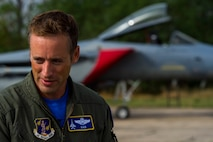 California Air National Guard Lt. Col. Matthew Ohman, a 194th Expeditionary Fighter Squadron F-15C Eagle fighter aircraft pilot, speaks during an interview with one of his squadron's aircraft in the background on the flightline during joint NATO air policing at Graf Ignatievo, Bulgaria, Sept. 9, 2016. Four California and Massachusetts ANGs' F-15Cs and approximately 75 Airmen from the 194th EFS deployed to Graf Ignatievo, Bulgaria, and will stand ready as interceptors, prepared to quickly react to any violations and infringements for policing of Bulgarian airspace Sept. 9-16, 2016. The squadron forward deployed to Graf Ignatievo from Campia Turzii, Romania, where they serve on a theater security package deployment to Europe as a part of Operation Atlantic Resolve.  (U.S. Air Force photo by Staff Sgt. Joe W. McFadden/Released)