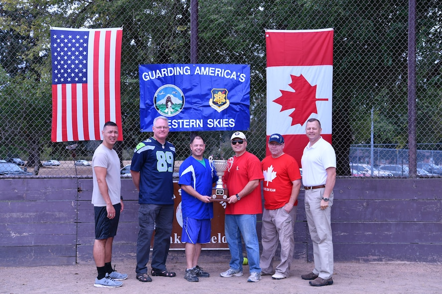 The Western Air Defense Sector's CAN-AM Challenge Cup was officially passed from Canadian Detachment commander, Lt. Col. Matthew Wappler, to Chief Master Sgt. Daniel Rebstock, 225th Support Squadron superintendent, after the U.S. won the annual softball game by a final score of 22 to 7.  Pictured from left to right are: Chief Master Sgt. Allan Lawson, Col. William Krueger, Chief Master Sgt. Daniel Rebstock, Canadian Lt. Col. Matthew Wappler, Canadian Warrant Officer Richard Martin, and Col. Gregor Leist. (U.S. Air National Guard photo by Capt. Kimberly D. Burke)