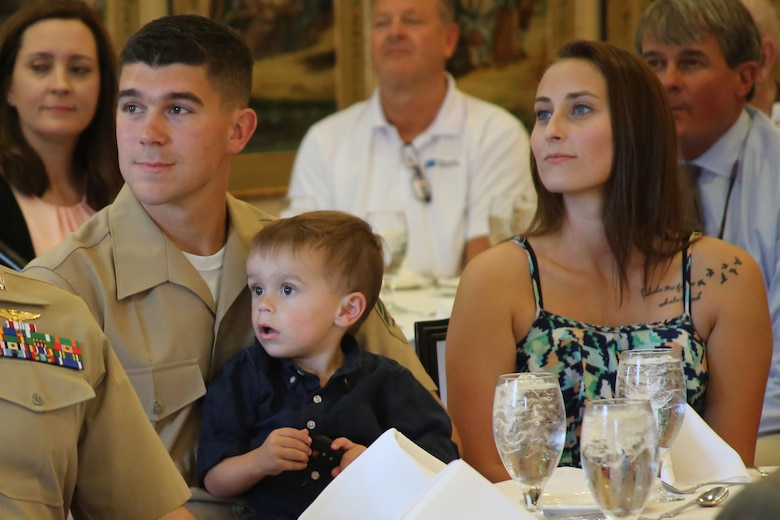 Cpl. Jared Hall (left) listens to a guest speaker with his wife, Erin, and son, Riley, during a reception at the New Bern Country Club to receive the Military Family of the Quarter Award in New Bern, N.C., Sept. 8. The Hall family received the Military Family of the Quarter Award during the reception. The family received awards, gifts, and gift certificates from the Havelock Military Affairs Committee and the New Bern Military Alliance Committee in appreciation for their service. Hall is an aviation communications technician with Marine Air Support Squadron 1. (U.S. Marine Corps photo by Lance Cpl. Mackenzie Gibson/Released)