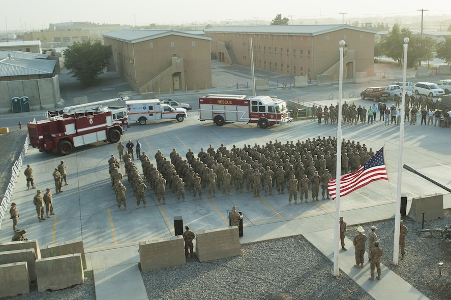 Service members and civilians gather for a 9/11 remembrance ceremony