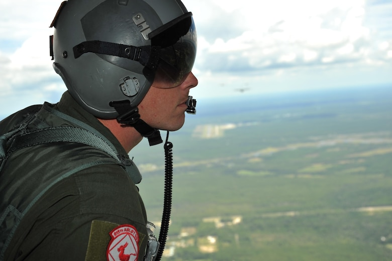 Master Sgt. Chris Sentilles, 815th Airlift Squadron loadmaster, looks out the back of one of the squadrons C-130J cargo aircraft during a four-aircraft training mission Sept. 11, 2016, over the Mississippi Gulfcoast. The aircraft took off from Keesler Air Force Base, Mississippi, and airdropped simulated cargo and heavy equipment over Stennis International Airport, Mississippi. (U.S. Air Force photo/Tech. Sgt. Ryan Labadens)