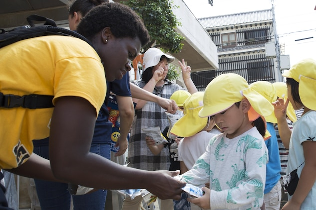 U.S. Navy Chief Petty Officer select Lamonica Harrison, chief hospital corpsman select with the Branch Health Clinic on Marine Corps Air Station Iwakuni, hands juice to a local Japanese child at Ekimae Hoikuen preschool in Iwakuni, Japan, Sept. 8, 2016. After completing the maintenance at the school, the Seabees provided drinks and chips to the students and had the opportunity to talk with them about the maintenance they completed. (U.S. Marine Corps photo by Lance Cpl. Joseph Abrego)