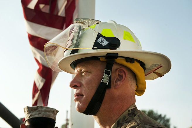 A Defense Department civilian firefighter participates during the lowering of the American flag to half-staff during a 9/11 remembrance ceremony at Bagram Airfield, Afghanistan, Sept. 11, 2016. Air Force photo by Capt. Korey Fratini