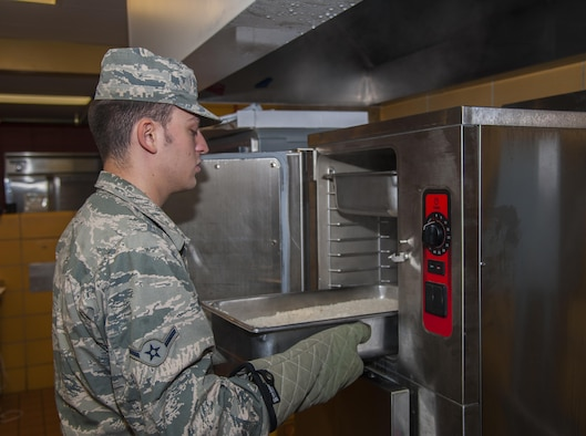 A 5th Force Support Squadron cook, pulls rice from the steamer before lunch at Minot Air Force Base, N.D., Sept. 7, 2016. The new dining facility now offers more food options including a pizza station, an entrée line, and a rotating bar of Mongolian grill, pasta, quesadillas and a sub sandwich bar. (U.S. Air Force photo/Airman 1st Class Christian Sullivan)