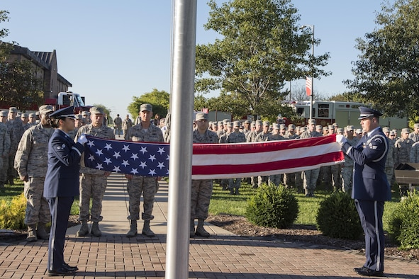 Senior Airman Stephanie Briones, Grissom base honor guard manager, and Senior Airman Ryan Ware, Grissom Base honor guard member, perform a flag folding ceremony during a 9/11 remembrance ceremony at Grissom Air Reserve Base, Ind., Sept. 11, 2016. During the event more than 500 Grissom Airmen, firefighters and civilians joined Americans around the world to share a moment of silence to remember the victims and pay their respects. (U.S. Air Force photo/Tech. Sgt. Benjamin Mota)