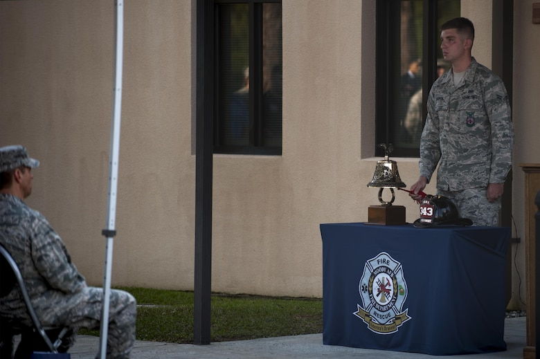 U.S. Air Force Airman 1st Class Nicholas Gough, 23d Civil Engineer Squadron firefighter, rings a ceremonial firefighter's bell during a 9/11 memorial ceremony, Sept. 11, 2016, at Moody Air Force Base, Ga. As firefighter tradition, three rings represent honor and respect for those who have given their lives while serving others. (U.S. Air Force photo by Airman 1st Class Daniel Snider)