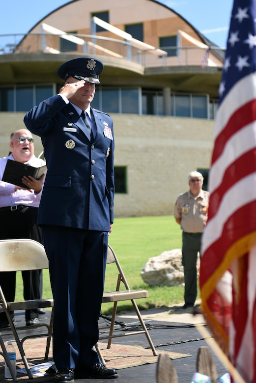 U.S. Air Force Col. Michael Downs, 17th Training Wing Commander, salutes the American flag for the National Anthem during the San Angelo 9/11 Remembrance Ceremony at the Fine Arts Museum in San Angelo, Texas, Sept. 11, 2016. A local public school band and community choir performed the National Anthem for the ceremony. (U.S. Air Force photo by Airman 1st Class Caelynn Ferguson/Released)