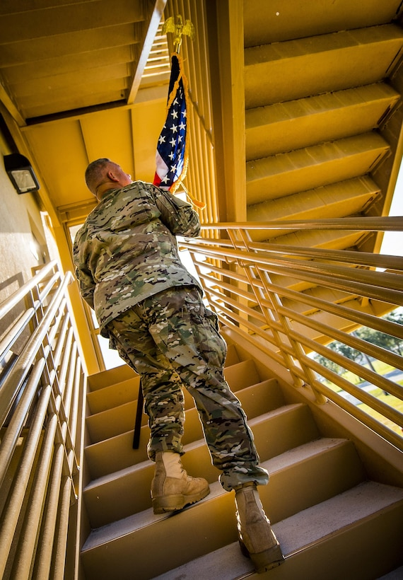 An Airman carries an American flag up a flight of stairs during a 9/11 Memorial Stair Climb event held at Duke Field, Fla., Sept. 10.  The 24-hour climb began at 8:46 a.m. with the 919th Special Operations Wing commander walking the flag up the outside stairwell of the base's billeting facility.  Wing Airmen took turns walking the flag up and down the stairwell the entire day until it was delivered to a firefighter and security forces color guard at 8:46 a.m. the next morning for a 9/11 Remembrance ceremony. More than 115 Airmen carried the flag throughout the day and night for a total of more than 207,000 steps. (U.S. Air Force photo/Tech. Sgt. Sam King)