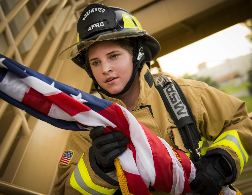 Senior Airman Raquelle Lockaby, 919th Special Operations Civil Engineer Squadron, carries an American flag up a flight of stairs while wearing her firefighting gear during a 9/11 Memorial Stair Climb event at Duke Field, Fla., Sept. 11.  The 24-hour climb began at 8:46 a.m. Sept. 10 with the 919th Special Operations Wing commander walking the flag up the outside stairwell of the base's billeting facility.  Wing Airmen took turns walking the flag up and down the stairwell the entire day until it was delivered to a firefighter and security forces color guard at 8:46 a.m. the next morning for a 9/11 Remembrance ceremony. More than 115 Airmen carried the flag throughout the day and night for a total of more than 207,000 steps.  (U.S. Air Force photo/Tech. Sgt. Sam King)