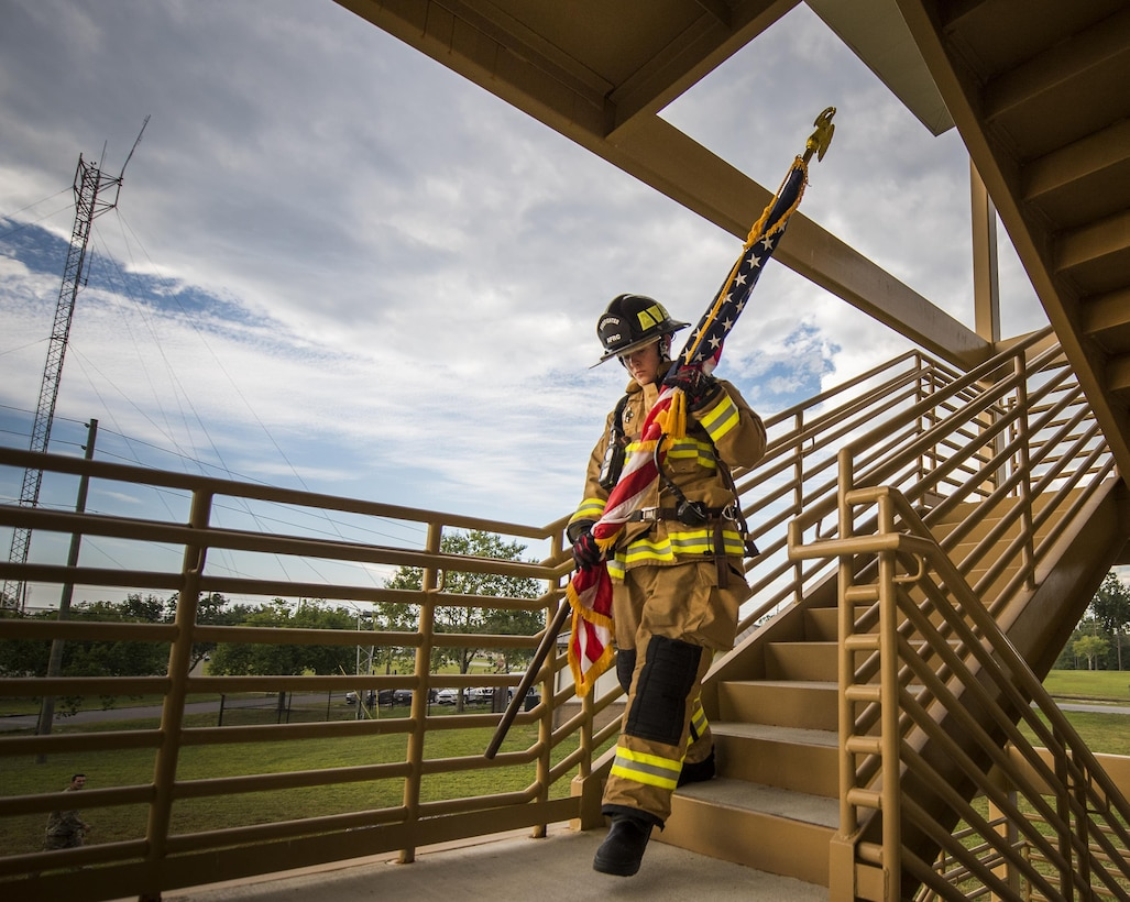 Airman Virginia Davis, 919th Special Operations Civil Engineer Squadron, carries an American flag down a flight of stairs while wearing her firefighter gear during a 9/11 Memorial Stair Climb event at Duke Field, Fla., Sept. 11.  The 24-hour climb began at 8:46 a.m. Sept. 10 with the 919th Special Operations Wing commander walking the flag up the outside stairwell of the base's billeting facility.  Wing Airmen took turns walking the flag up and down the stairwell the entire day until it was delivered to a firefighter and security forces color guard at 8:46 a.m. the next morning for a 9/11 Remembrance ceremony.  More than 115 Airmen carried the flag throughout the day and night for a total of more than 207,000 steps.  (U.S. Air Force photo/Tech. Sgt. Sam King)